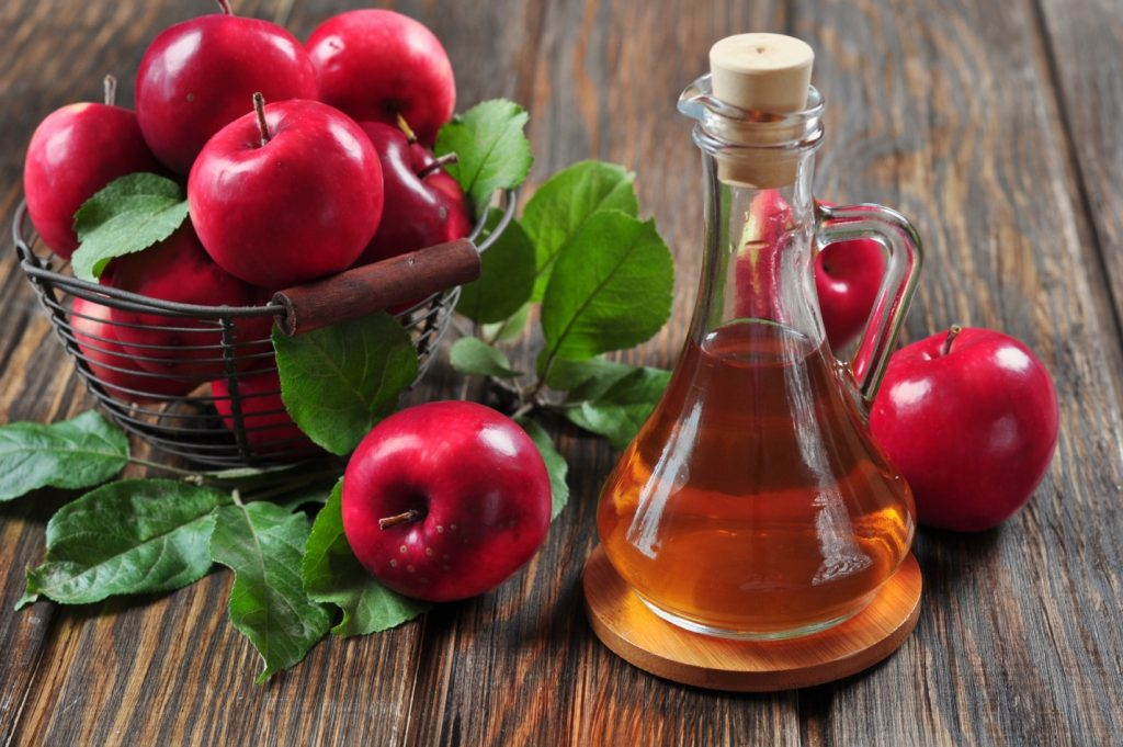 Яблоки в коринке и бутылочка яблочного уксуса